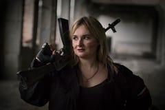 En flicka med en maskingevär royaltyfria bilder