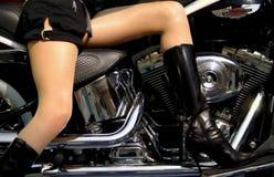 En flicka med mjuk hud på den svarta motorcykeln Fotografering för Bildbyråer