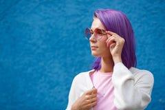 En flicka med purpurfärgat hår i rosa exponeringsglas royaltyfri foto