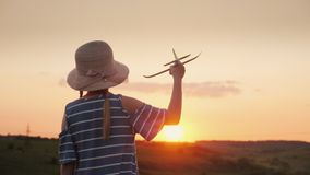En flicka med råttsvansar och en hatt som spelar med ett träflygplan på solnedgången Drömmen av det långdistans- loppet är ett be Royaltyfri Bild
