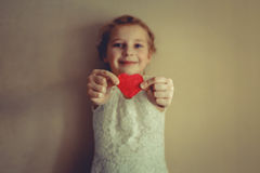 En flicka med röd hjärta i henne händer Royaltyfri Foto