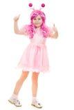 En flicka med rosa hår i en rosa klänning visar okay royaltyfri bild