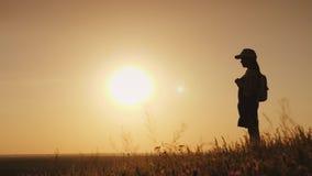 En flicka med en ryggsäck är i ett pittoreskt ställe som framåtriktat ser till solnedgången Lite handelsresande och en barn` s fotografering för bildbyråer