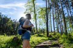 En flicka med en ryggsäck går till och med skogen Arkivbild