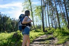En flicka med en ryggsäck går till och med skogen Royaltyfria Bilder
