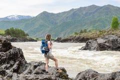 En flicka med en ryggsäck står på banken av en bergflod Arkivbild