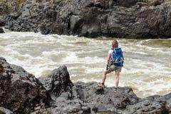 En flicka med en ryggsäck står på banken av en bergflod Royaltyfri Bild