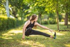 En flicka med ursnyggt och härligt långt ljus - brunt hår gör sportövningar En idrotts- idrottskvinna gör övning Fotografering för Bildbyråer