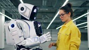 En flicka och en cyborg trycker på händer arkivfilmer