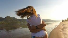 En flicka och en grabb som omkring kör på stranden arkivfilmer
