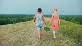 En flicka och en pojke bär korgar av bär tillsammans De promenerar den pittoreska bygden Steadicam skott, baksida arkivfilmer
