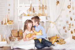 En flicka och en pojke i guld- julpynt Royaltyfria Bilder