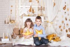 En flicka och en pojke i guld- julpynt Arkivfoton
