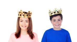 En flicka och en pojke med guld- kronor på deras huvud Royaltyfria Bilder