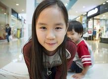 En flicka och en pojke som ler på shoppinggallerian Royaltyfri Bild