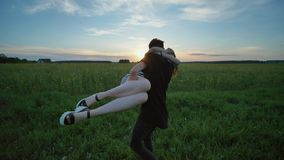 En flicka och en grabbkörning till ett möte och omfamning på solnedgången lager videofilmer