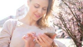 En flicka och en smartphone, en stående på en stadsgata mot bakgrunden av att blomma magnoliaträd, solen är stock video
