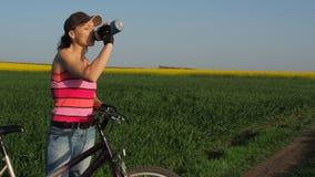 En flicka på en cykel dricker vatten Ung kvinna i en bygd med en cykel En sportflicka är dricksvatten arkivfilmer
