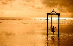 En flicka på en gunga över havet på solnedgången i bali, indonesia 2 Arkivfoton
