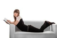 En flicka på en soffaläsning Royaltyfria Bilder