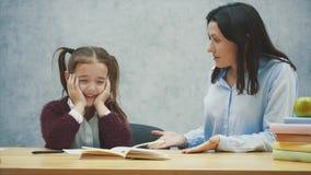 En flicka på en grå bakgrund sitter på tabellen och skriken Under detta grälar min moder med hennes dotter Begrepp arkivfilmer