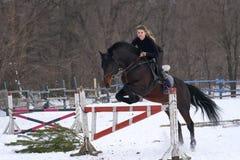 En flicka på en häst hoppar över barriären Utbildningsflickajockey som rider en häst En molnig vinterdag Arkivbild
