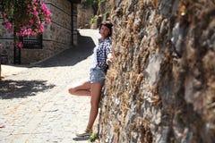 En flicka poserar för en kamera i en gammal stadsgata som stenläggas med förberedande stenar Royaltyfri Bild