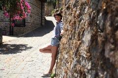 En flicka poserar för en kamera i en gammal stadsgata som stenläggas med förberedande stenar Arkivfoton