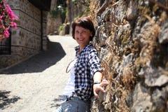 En flicka poserar för en kamera i en gammal stadsgata som stenläggas med förberedande stenar Royaltyfri Fotografi