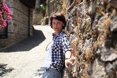 En flicka poserar för en kamera i en gammal stadsgata som stenläggas med förberedande stenar Royaltyfria Bilder