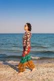 En flicka promenerar stranden Fotografering för Bildbyråer