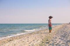 En flicka promenerar stranden Arkivfoto