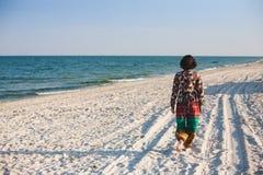 En flicka promenerar stranden Arkivbilder