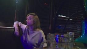 En flicka röker en vattenpipa och dricker öl på en nattklubb lager videofilmer