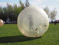 En flicka rullar ner i en jätte- bubblaboll för utomhus- uppblåsbara lekar royaltyfri bild