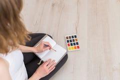 En flicka rymmer en borste i hennes hand och drar med vattenfärgmålarfärg arkivfoton