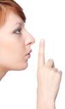 En flicka rymmer ett finger till kanter gör en gest tyst fotografering för bildbyråer