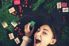 En flicka rymmer en gåva och le för jul Royaltyfria Foton