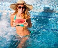 En flicka rymmer halva en röd vattenmelon över en blå pöl, avslappnande nolla royaltyfri fotografi