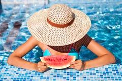 En flicka rymmer halva en röd vattenmelon över en blå pöl, avslappnande nolla royaltyfri bild
