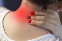 En flicka rymmer hennes hals, en smärtsam hals, en smärta, en röd fläck, en närbild vrider nacken av fotografering för bildbyråer