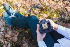 En flicka rymmer i hennes händer en gammal skog för filmfotokamera på våren royaltyfri bild