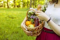 En flicka rymmer en korg av frukt för en picknick Gå på en picknick royaltyfria foton