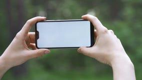 En flicka rymmer en smart telefon på en suddig naturlig bakgrund Begrepp - mobil internet, smartphone i natur arkivfilmer