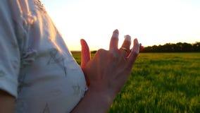 En flicka rymmer en smartphone i henne handnärbilden på en solnedgångbakgrund på en grön gräsmatta i ultrarapid stock video