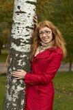 En flicka satte hennes armar runt om stammen av ett träd för björk t med bärande exponeringsglas för guld- hår i ett ljust för som arkivfoto
