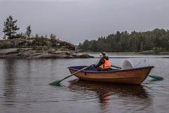 En flicka seglar bara i ett fartyg i mitt av en sjö fotografering för bildbyråer