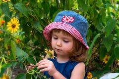 En flicka ser en gul blomma Arkivfoto