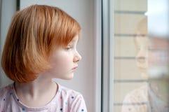 En flicka ser in i hennes reflexion i ett fönster royaltyfri foto