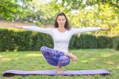 En flicka ser sund, sportig och gör fysisk övning En kvinna sitter på ett ben och fördelar hennes händer till sidorna Royaltyfri Bild